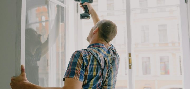 handyman installing window frame with drill in house